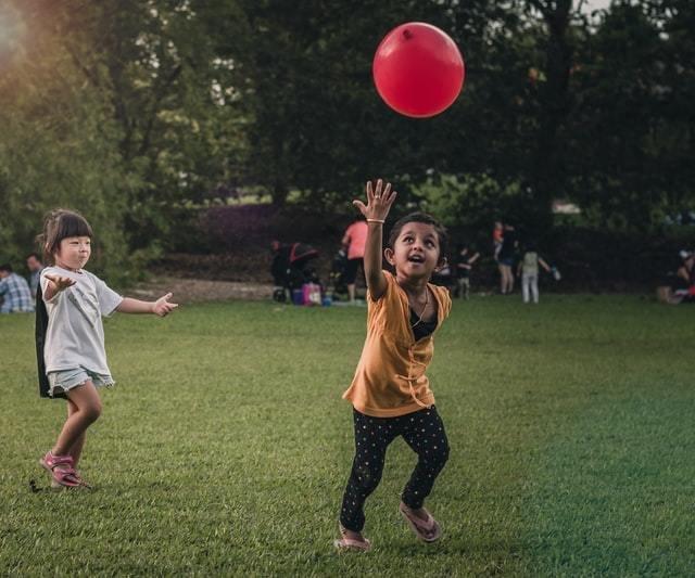 Duas crianças brincam com uma bexiga vermelha sobre o gramado