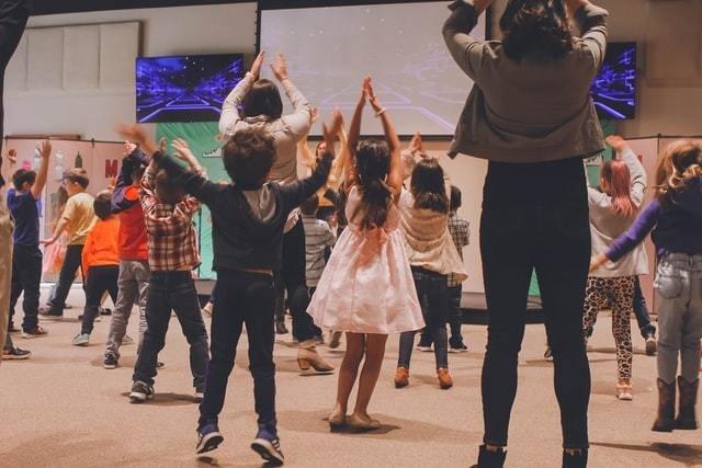 Crianças dançam de costas para a câmera