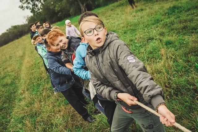 Meninos brincam de cabo-de-guerra em lugar a céu aberto