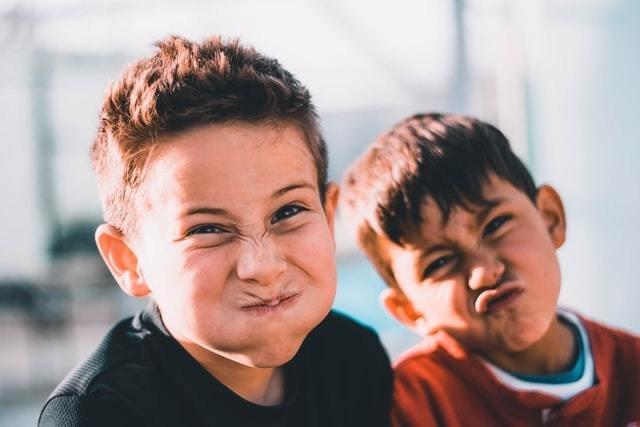 Dois meninos fazem careta para a foto