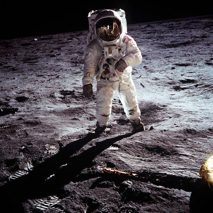 Astronauta pisando no solo lunar com imagem de colegas refletindo no capacete