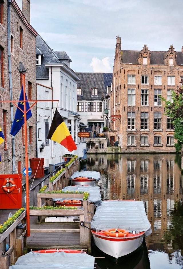 Rio com barcos parados, bandeira da Bélgica e da União Europeia