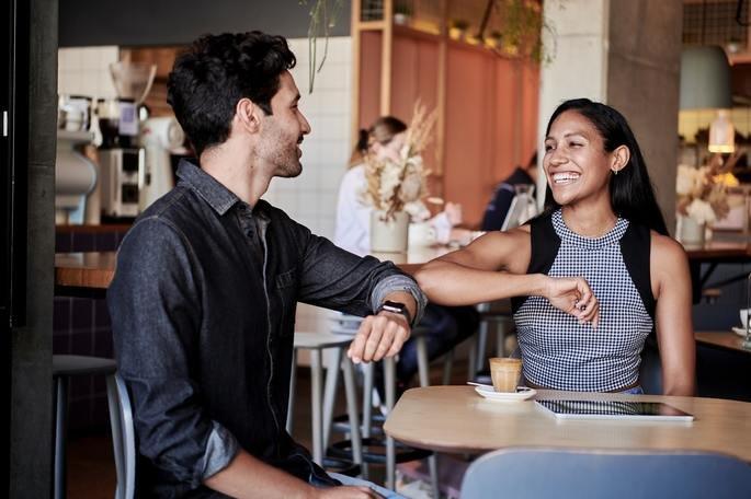 Mulher e homem sentados em uma mesa se cumprimentam com os cotovelos