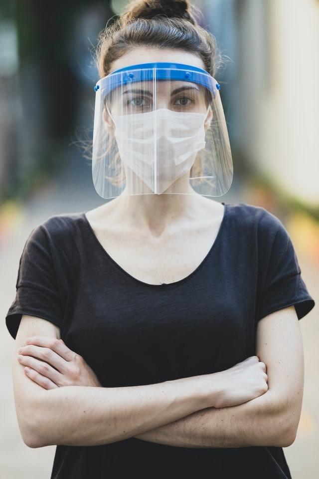 Mulher veste máscara e face shield