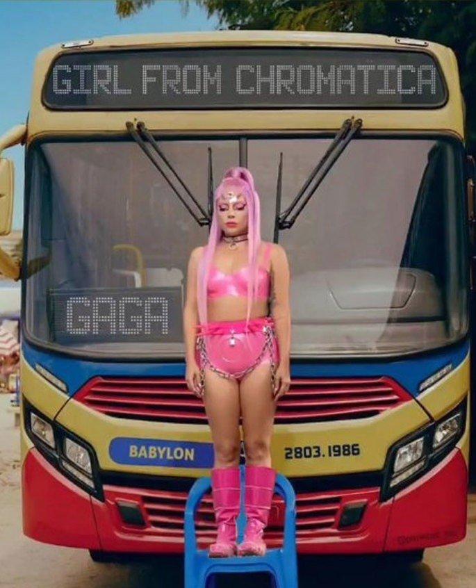 Lady Gaga em pé em uma cadeira de plástico azul em frente a um ônibus
