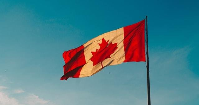 Bandeira do Canadá tremulando ao vento com céu azul ao fundo