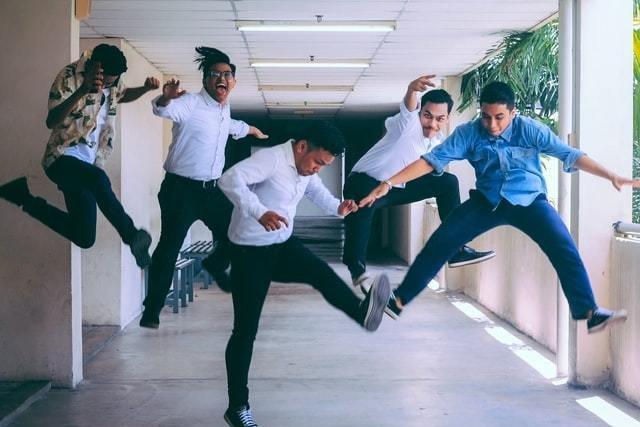 Grupo de homens ri enquanto saltam em um corredor