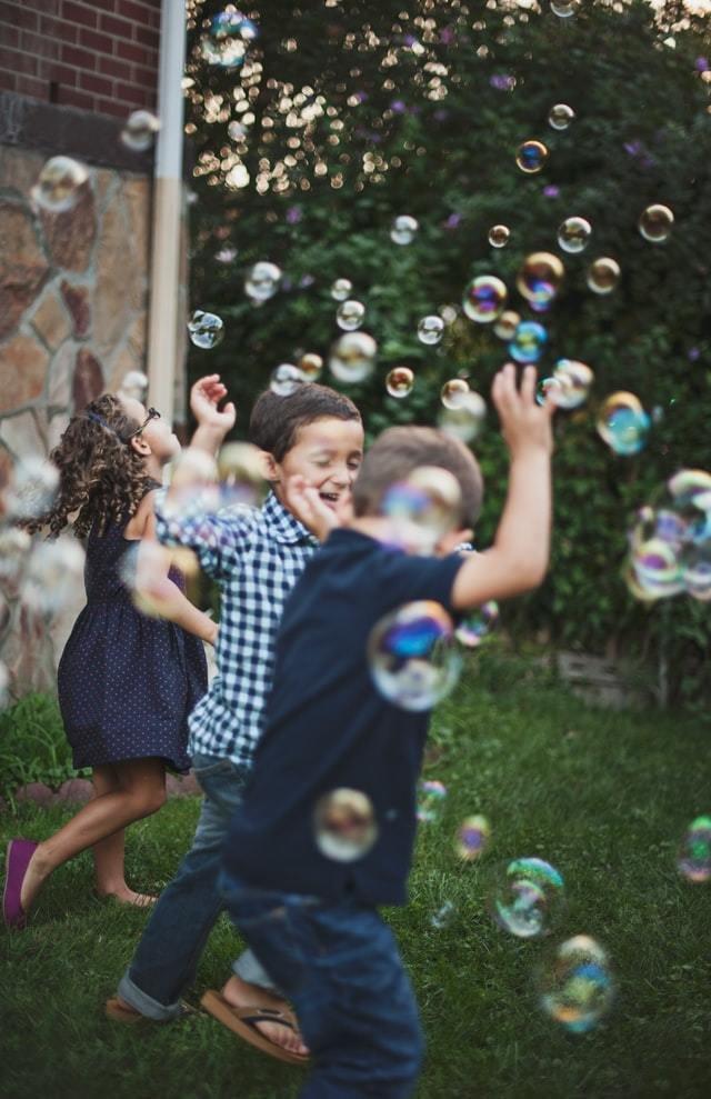 Crianças brincam ao ar livre estourando bolhas de sabão