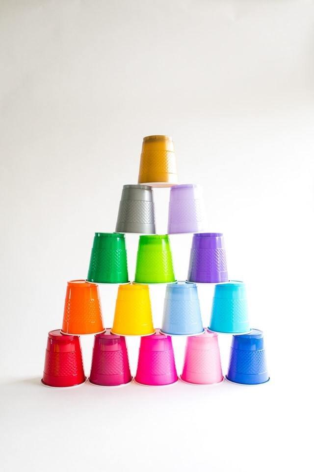 Torre de copos descartáveis coloridos em frente a uma parede clara