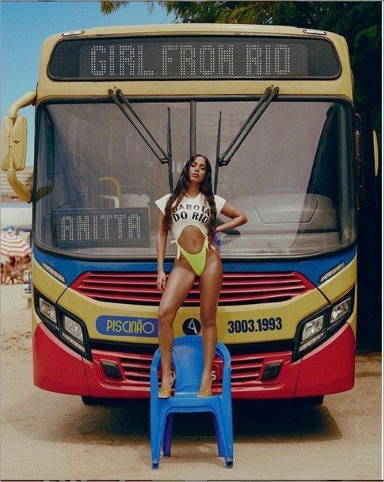 Anitta em pé em uma cadeira de plástico azul em frente a um ônibus