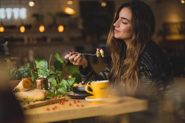 Mulher sorri enquanto segura garfo com massa