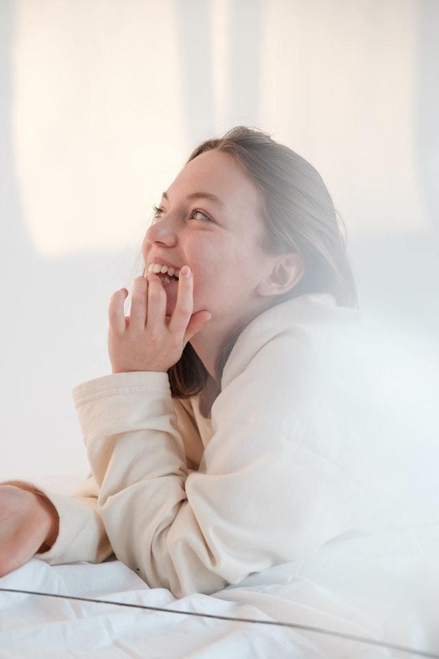 Mulher jovem morde as unhas, vestida de casaco branco em um fundo claro