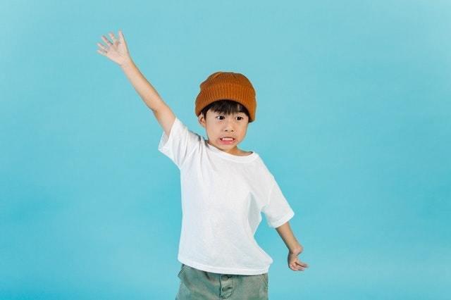 Menino de gorro laranja abre os braços em frente a um fundo azul claro
