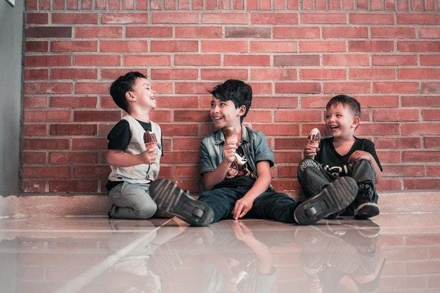 Três meninos sentados no chão tomando sorvete e rindo