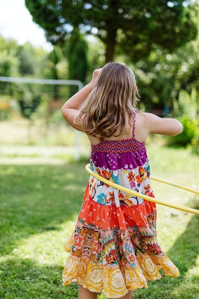 Menina de vestido estampado roda bambolê na cintura em um parque