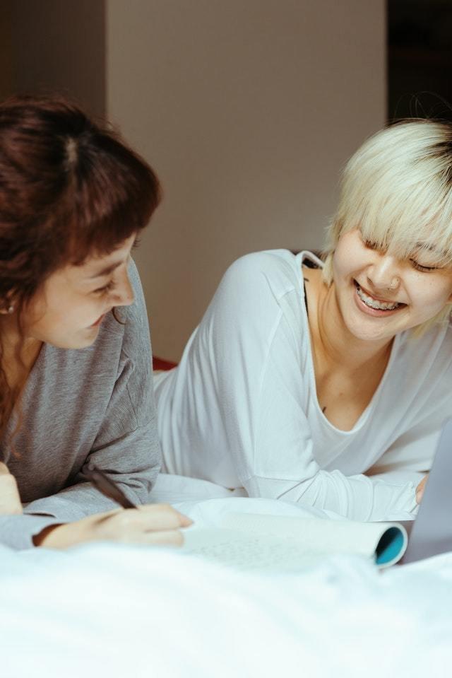 Duas mulheres deitadas sobre uma cama com um caderno e um notebook