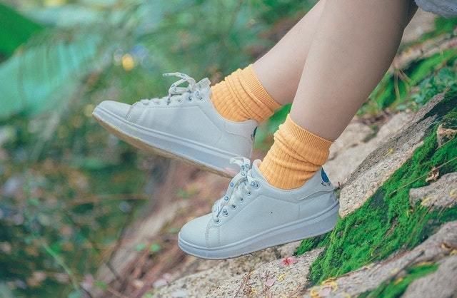 Pés calçando tênis brancos e meias amarelas