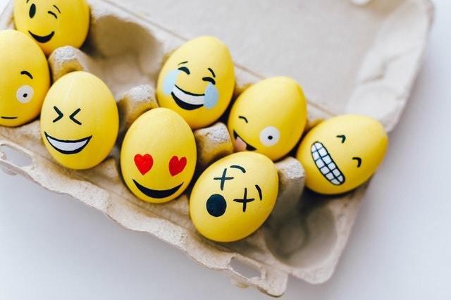 ovos pintados de emojis dentro de uma caixa de ovos