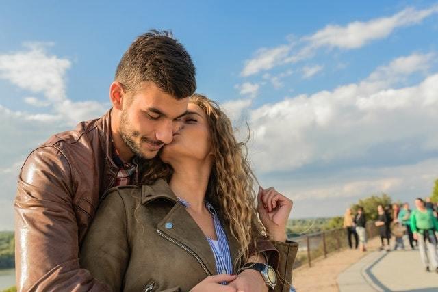 Casal ao ar livre. Menina dá um beijo na bochecha do rapaz.