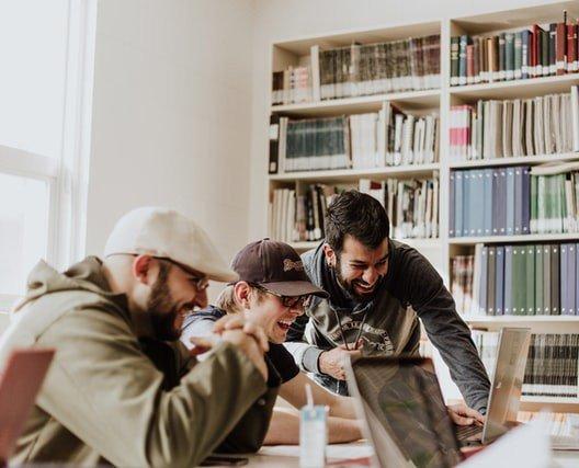 Três homens sorriem enquanto olham para a tela do computador em uma sala