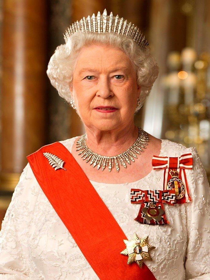 Foto oficial da Rainha Elizabeth II de coroa, roupa branca e faixa vermelha