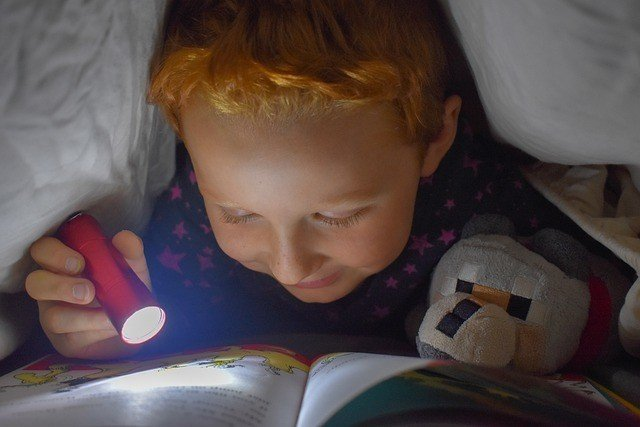 Menino ruivo lê livro com lanterna embaixo das cobertas