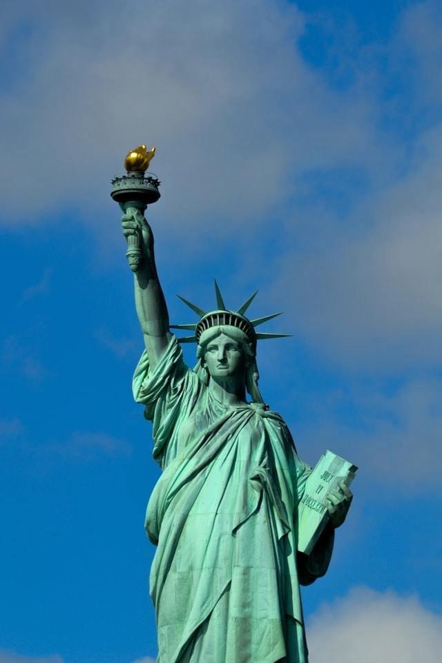 Estátua da Liberdade de frente com céu azul ao fundo
