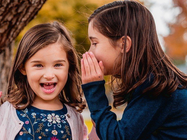 Menina fala no ouvido de outra, que sorri surpresa