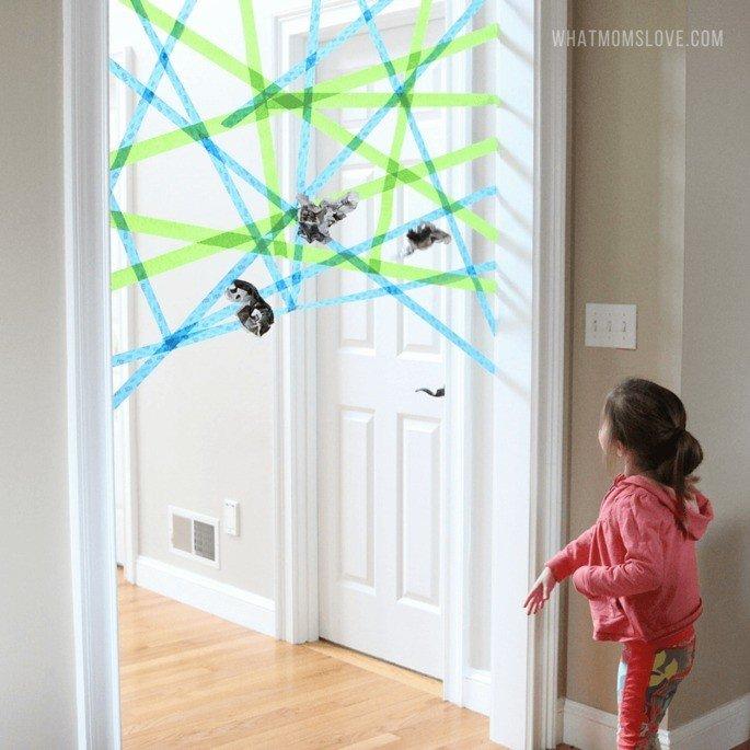 Teia feita com fita adesiva em porta em que criança joga pedaços de papel