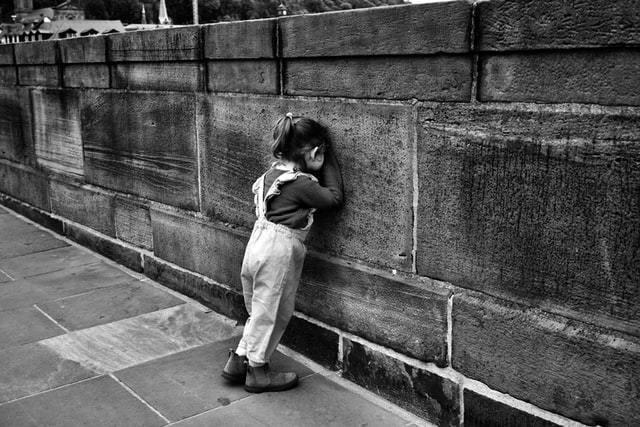 Criança conta encostada na parede  em foto em preto e branco