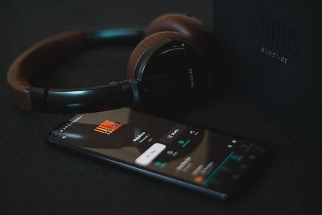 Smartphole com player de música aberto com um headphone em cima